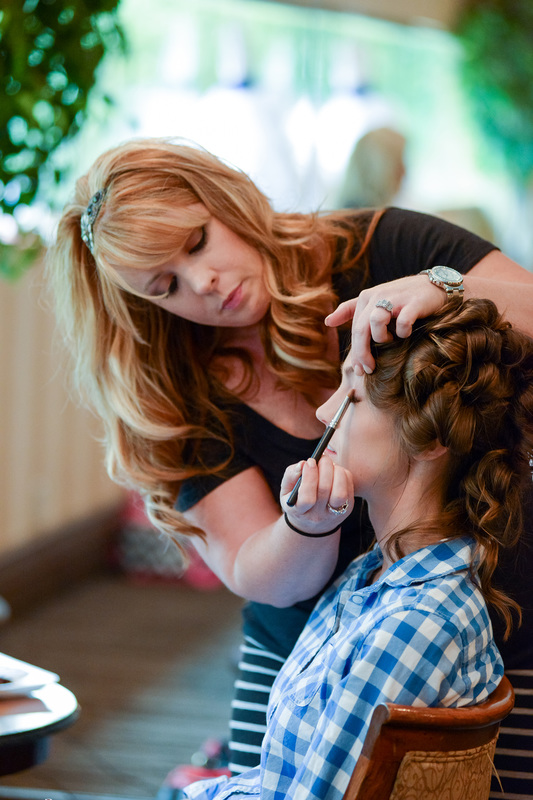 A candid picture of Updo's Studio's owner, Amanda Wazlavek, doing a bride's makeup.