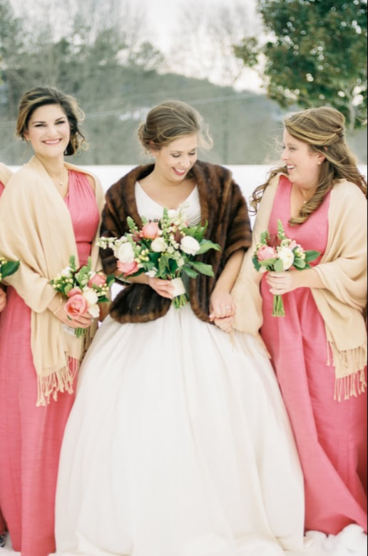A bridal party with complete hair and makeup and clad in pink dresses laughing together.